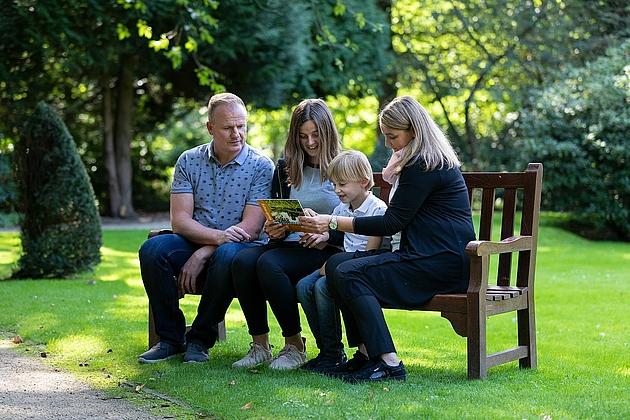 Familie verweilt auf einer Parkbank im Schlosspark