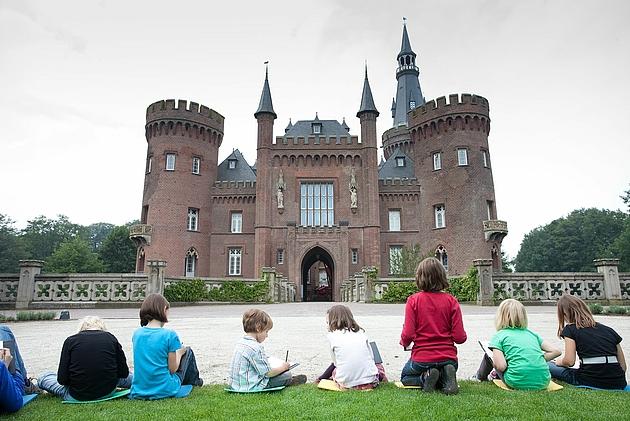 Kinder sitzen zeichnend vor dem Schloss