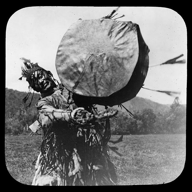 Foto eines Schamanen mit traditioneller Kleidung und Trommel