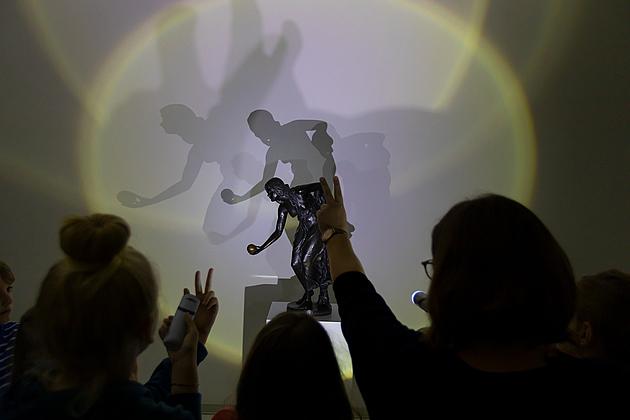 Kinder leuchten mit Taschenlampe auf Kunstwerk, das Schatten wirft