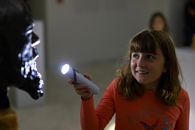 Taschenlampenführung: Ein Mädchen strahlt mit der Taschenlampe eine Bronzeskulptur an