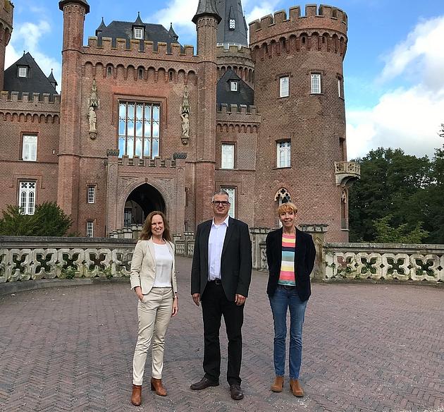 3 Personen stehen vor Schloss Moyland