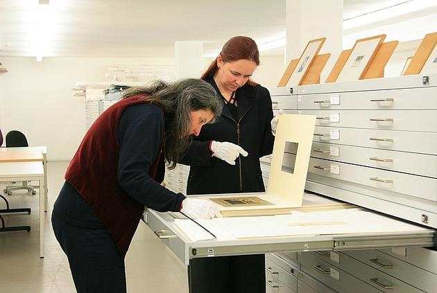 Mitarbeiterinnen mit Handschuhen bei Begutachtung eines Dokumentes im Depot