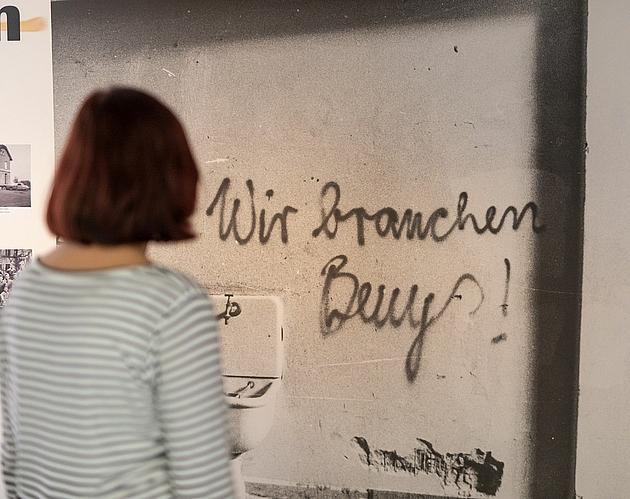 """Besucherin vor dem Foto eines Graffitis mit dem Satz """"Wir brauchen Beuys"""""""