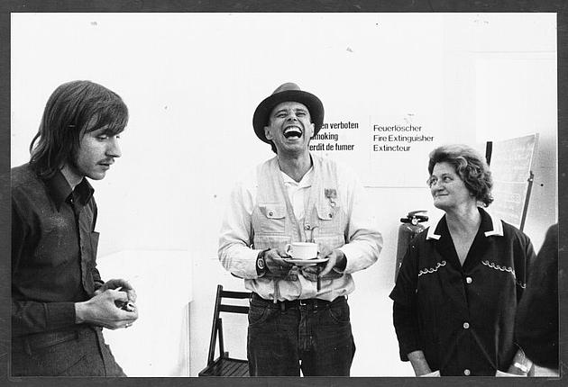 schwarz-weiß Bild mit 3 Personen, in der Mitte Joseph Beuys, lachend mit Tasse in Hand
